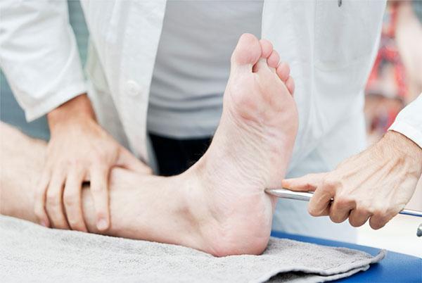 Lekarz badający stopę klienta
